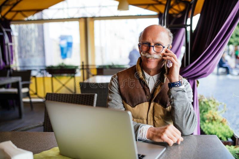 Retrato do homem superior que fala pelo telefone que sorri felizmente ao trabalhar com o portátil na sala de estar exterior do ca imagem de stock