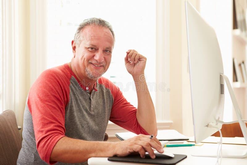 Retrato do homem superior que usa o computador em casa imagem de stock