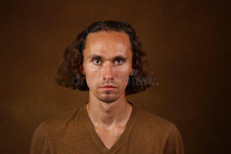 Retrato do indiv?duo ? moda com o cabelo longo que veste o t-shirt marrom que olha com seus olhos marrons na c?mera fotografia de stock