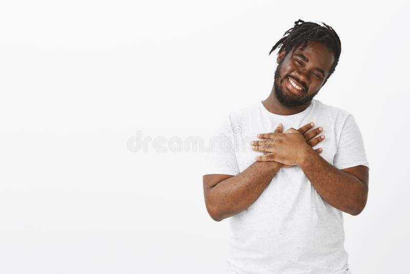 Retrato do indivíduo afro-americano gordo bonito satisfeito com barba e bigode, inclinação principal e sorriso de reconfortante foto de stock