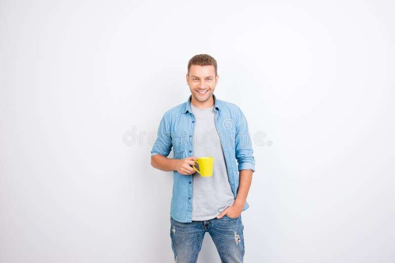 Retrato do indivíduo alegre, peppy que guarda a caneca amarela com café a fotografia de stock