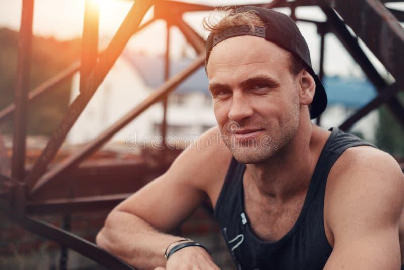 Retrato do indivíduo atlético que está no por do sol no telhado com construções enormes do metal fotografia de stock royalty free