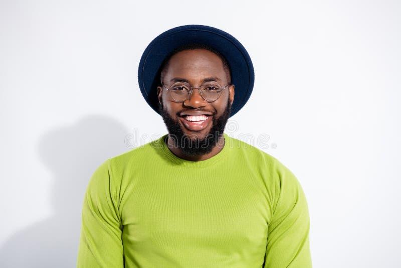 Retrato do indivíduo bonito que veste o pulôver verde que olha de sorriso sobre o fundo branco foto de stock