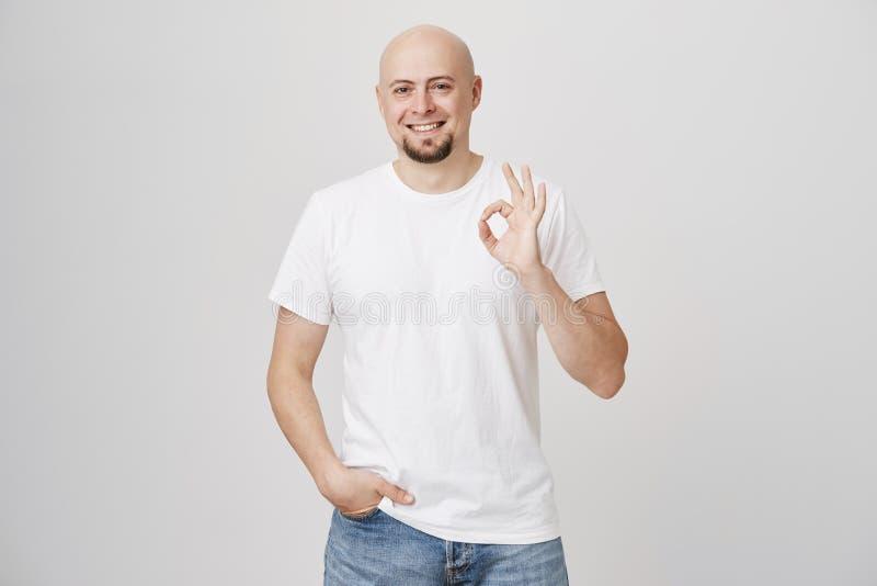 Retrato do indivíduo caucasiano farpado calvo bonito seguro que mostram está bem ou do gesto fino ao guardar a mão no bolso fotografia de stock