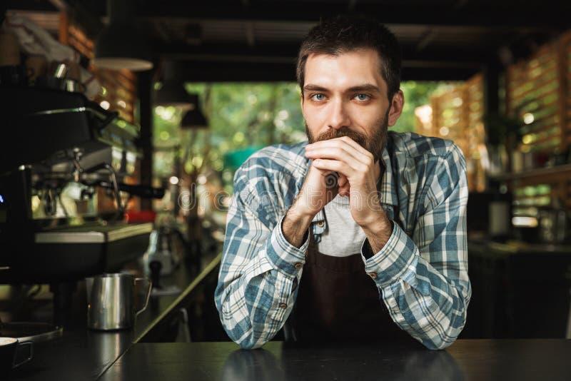 Retrato do indivíduo considerável do barista que sorri na câmera ao trabalhar no café ou no café da rua exterior fotografia de stock