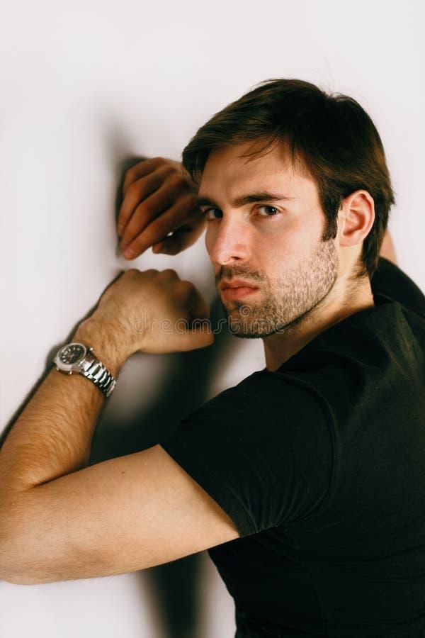Retrato do indivíduo considerável em um t-shirt e em um relógio pretos em uma mão fotos de stock