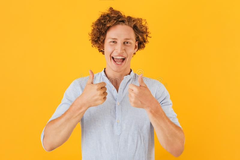 Retrato do indivíduo considerável entusiasmado 20s que sorri e que mostra os polegares foto de stock