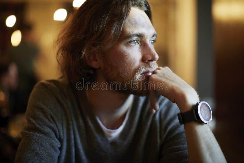 Retrato do indivíduo considerável do moderno com cabelo longo e da barba que senta-se no café ensolarado, descansando perto da ja imagens de stock