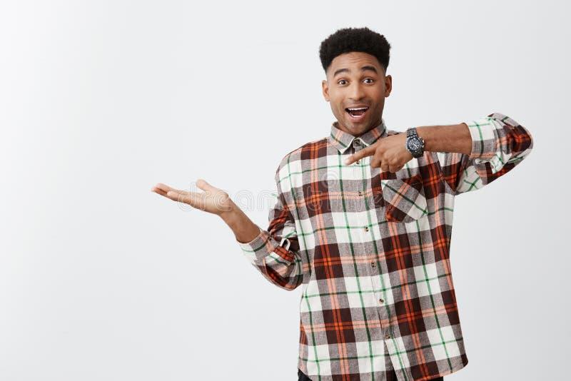 Retrato do indivíduo engraçado preto-descascado alegre novo com penteado afro na camisa ocasional quadriculado que finge guardar fotos de stock