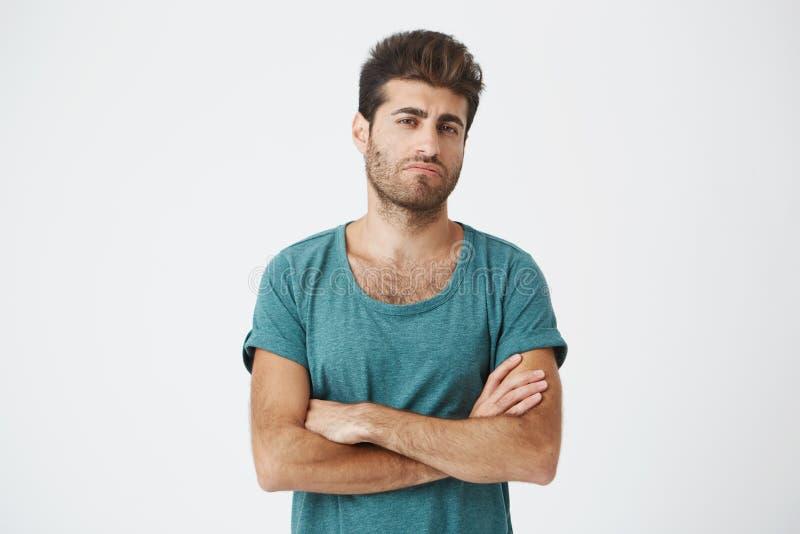 Retrato do indivíduo espanhol novo atrativo seguro no tshirt azul e no corte de cabelo à moda, mãos de cruzamento, sendo super imagens de stock royalty free