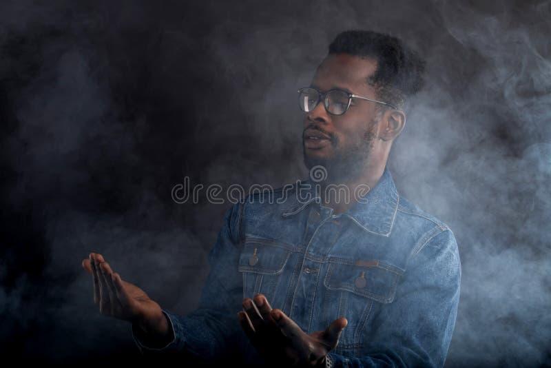 Retrato do indiv?duo africano no revestimento da sarja de Nimes na obscuridade imagens de stock