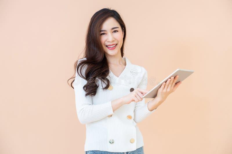 Retrato do Internet feliz de sorriso novo bonito da consultação da mulher no tablet pc digital isolado no fundo alaranjado fotos de stock royalty free