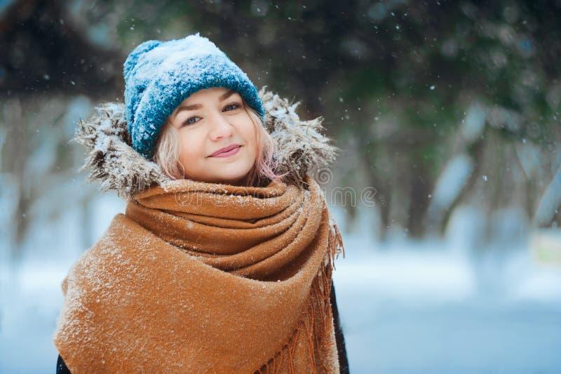 Retrato do inverno da jovem mulher feliz que anda na floresta nevado no equipamento morno, no chapéu feito malha e no lenço de ta foto de stock