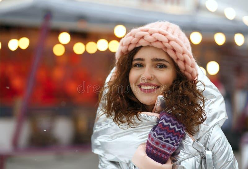 Retrato do inverno da jovem senhora moreno positiva que veste o equipamento na moda morno, andando na feira do Natal em Kyiv Espa imagem de stock