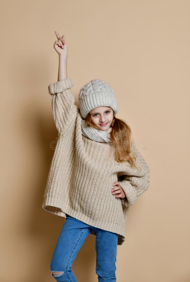 Retrato do inverno da menina feliz que veste o chapéu, o lenço e a camiseta feitos malha Criança no fundo de madeira branco Conce foto de stock royalty free