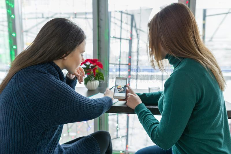 Retrato do inverno das jovens mulheres de fala que sentam-se em um café, olhando e discutindo fotos de um telefone celular, escol fotografia de stock
