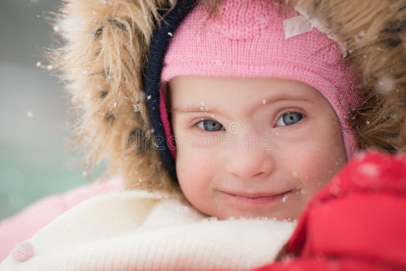 Retrato do inverno de uma menina bonita com Síndrome de Down imagens de stock royalty free