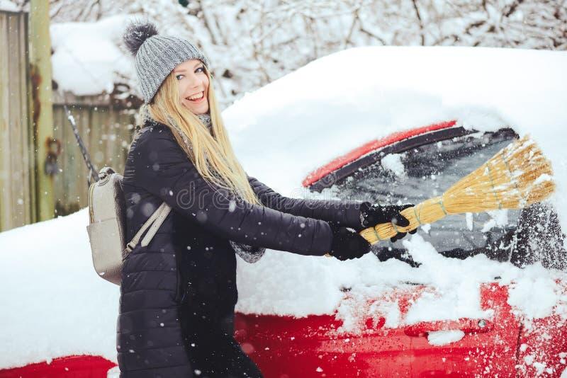 Retrato do inverno de uma neve da limpeza da jovem mulher de um carro A beleza Girl modelo louro ri e limpa alegremente a neve Be foto de stock royalty free