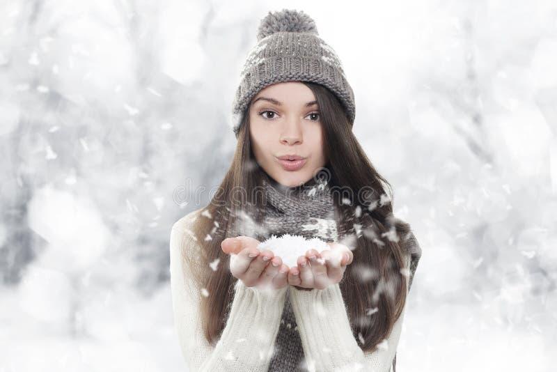 Retrato do inverno. Neve de sopro da mulher nova, bonita imagem de stock