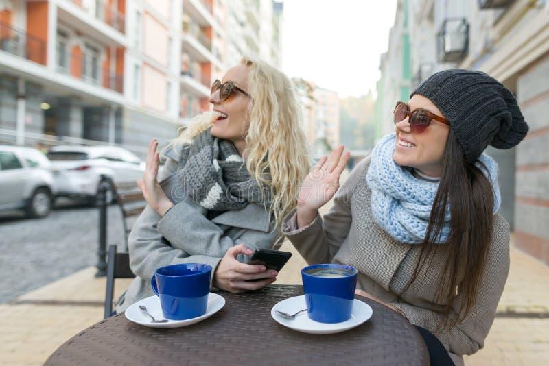 Retrato do inverno do outono de duas jovens mulheres em um café exterior, café bebendo, falando Fundo urbano fotos de stock royalty free