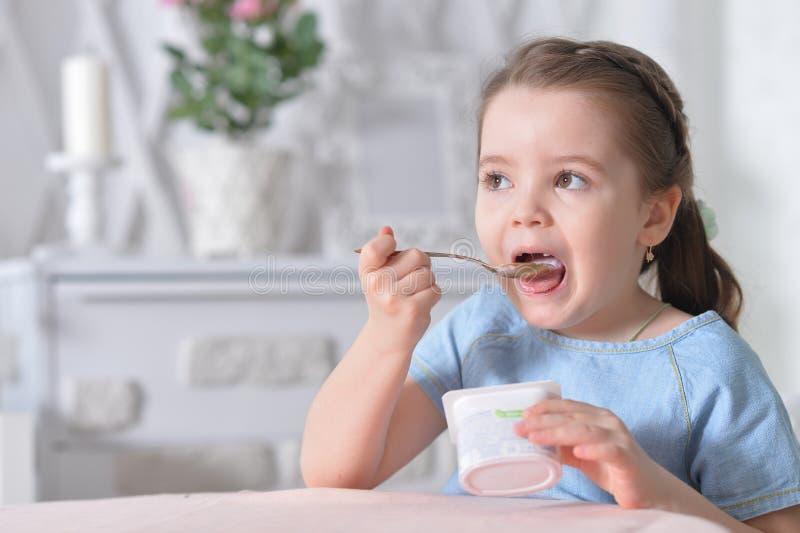 Retrato do iogurte delicioso comer bonito da menina fotos de stock royalty free