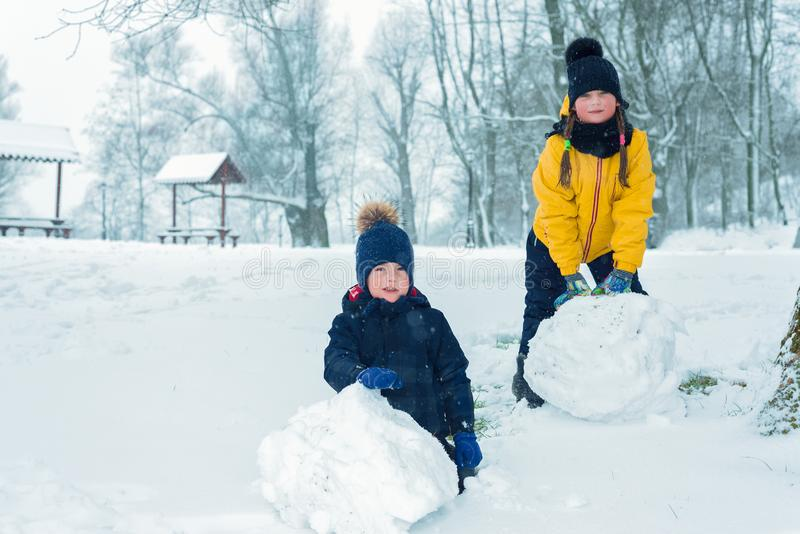 Retrato do irmão e da irmã o rapaz pequeno e a menina fazem o boneco de neve imagens de stock royalty free