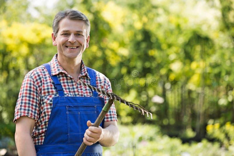 Retrato do jardineiro de sorriso que guarda o ancinho no berçário da planta imagem de stock