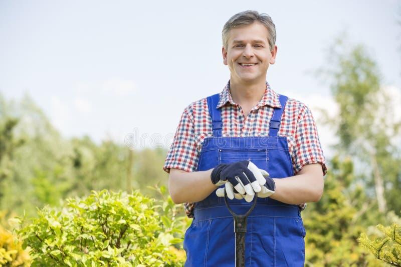 Retrato do jardineiro feliz que guarda a pá no berçário da planta imagem de stock royalty free