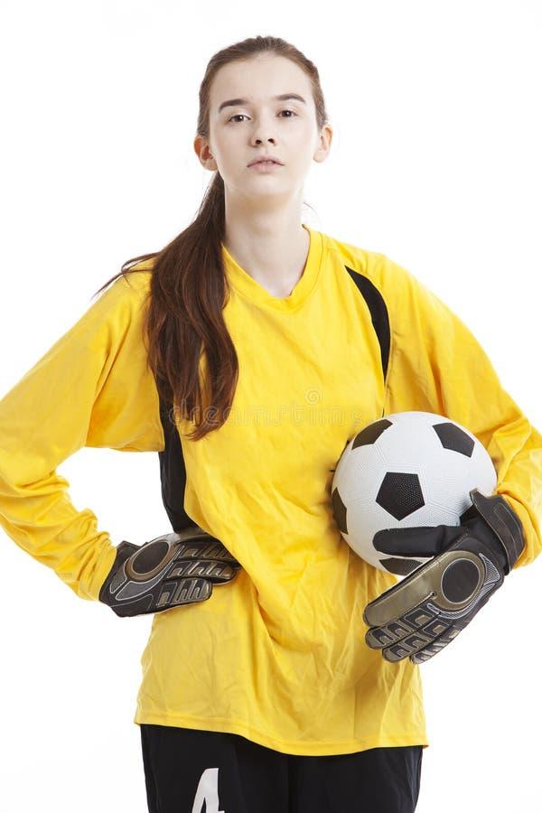 Retrato do jogador de futebol fêmea novo que mantém a bola com mão no quadril contra o fundo branco fotografia de stock