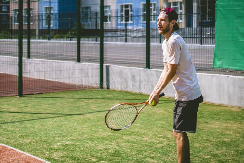 Retrato do jogador de tênis masculino novo na corte em um dia ensolarado fotografia de stock royalty free