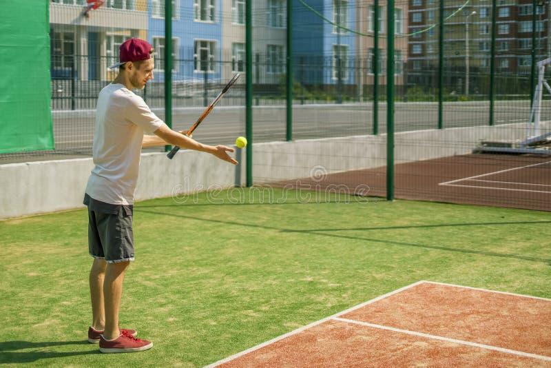 Retrato do jogador de tênis masculino novo na corte em um dia ensolarado imagem de stock