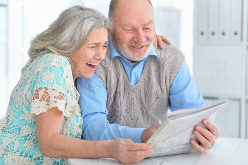 Retrato do jornal superior da leitura dos pares em casa imagem de stock royalty free