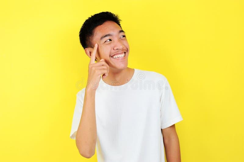 Retrato do jovem asiático esperto e feliz que pensa e olha para cima Feliz jovem asiático a usar camiseta branca a pensar e a olh fotos de stock