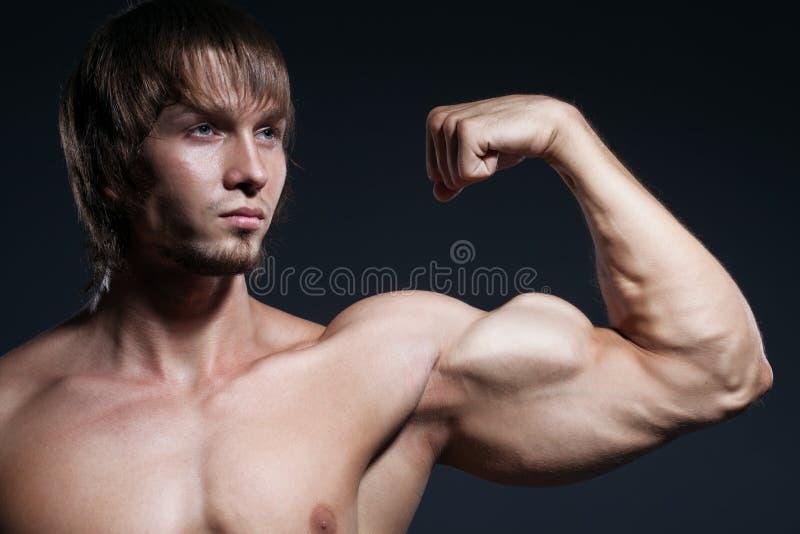 Retrato do levantamento modelo da aptidão atlética considerável saudável forte do homem perto da obscuridade - parede cinzenta fotos de stock royalty free