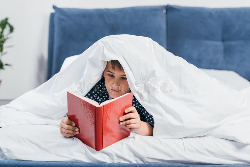 retrato do livro de leitura focalizado do rapaz pequeno ao encontrar-se sob a cobertura fotos de stock royalty free