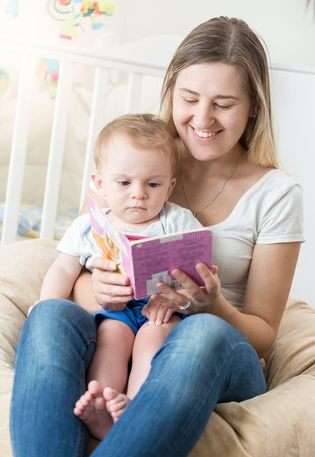 Retrato do livro de leitura de sorriso feliz da mãe do oyung a seu bebê fotos de stock