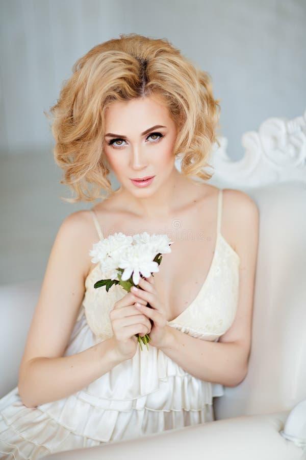 Retrato do louro macio sensual e 'sexy' que senta-se em um whit fotografia de stock