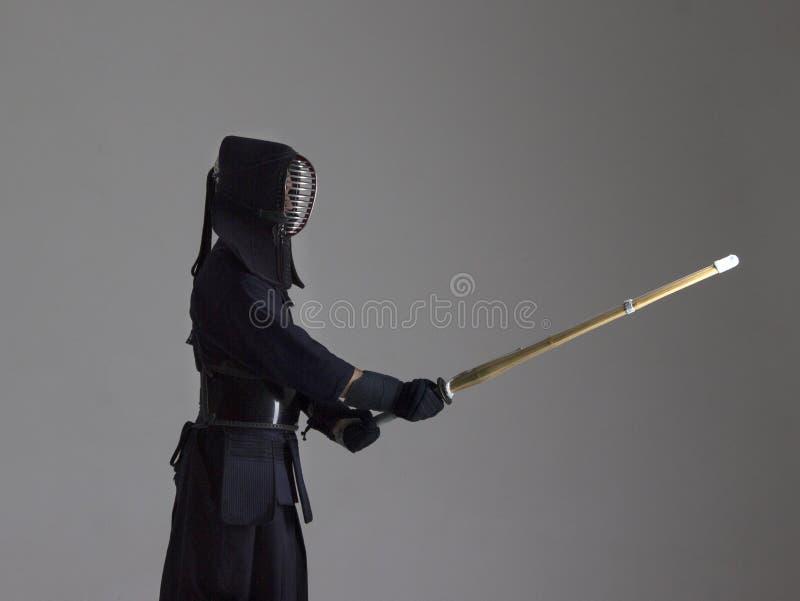 Retrato do lutador do kendo do homem com shinai Tiro do estúdio foto de stock royalty free