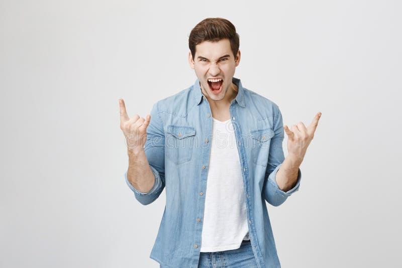 Retrato do músico considerável novo que grita e que faz o gesto da rocha com ambas as mãos ao apreciar o concerto emoções imagens de stock royalty free