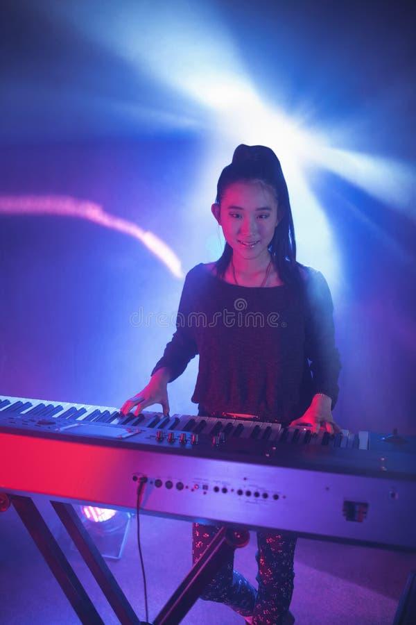 Retrato do músico fêmea de sorriso que joga o piano no clube noturno imagem de stock