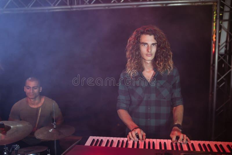 Retrato do músico masculino que joga o piano no clube noturno fotografia de stock