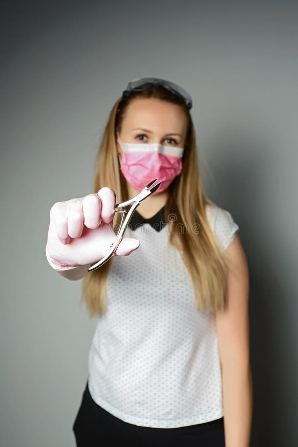 Retrato do manicuro profissional novo em luvas de borracha cor-de-rosa e na máscara médica que guardam a ferramenta do tratamento imagens de stock
