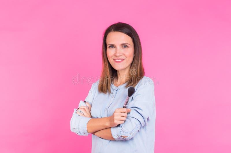 Retrato do maquilhador com escovas à disposição em um fundo cor-de-rosa imagens de stock