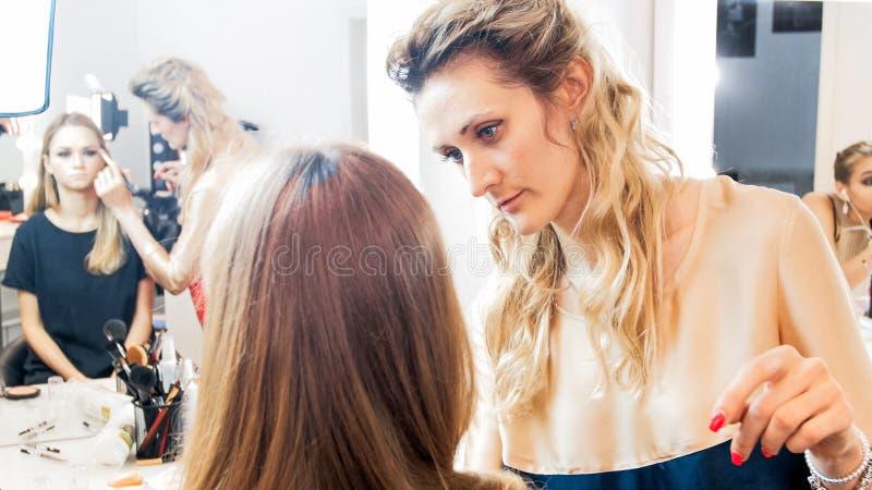 Retrato do maquilhador profissional que trabalha com modelo novo no estúdio fotografia de stock royalty free