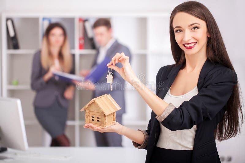 Retrato do mediador imobiliário com a família que obtém a casa nova Negócios imagens de stock royalty free