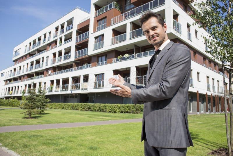 Retrato do mediador imobiliário seguro que mostra o prédio de escritórios foto de stock royalty free