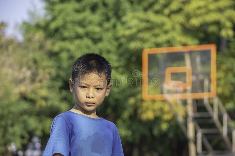 Retrato do menino asiático que sua o fundo da cara no campo de básquete fotografia de stock
