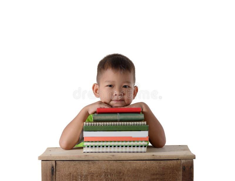 Retrato do menino asi?tico de sorriso do estudante pequeno com educa??o de muitos livros e conceito da escola isolado no fundo br imagem de stock
