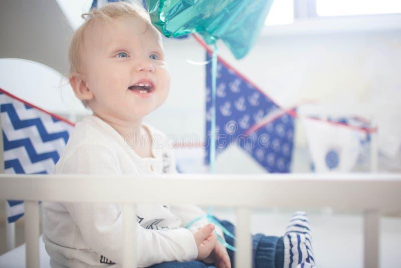 Retrato do menino do bebê de nove meses que sai os dentes e que levanta no berço branco fotos de stock royalty free