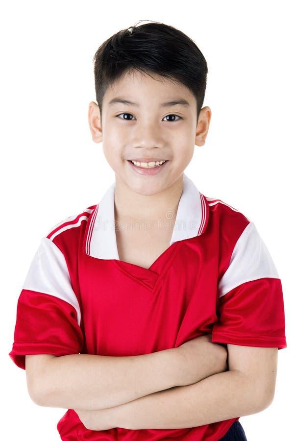 Retrato do menino bonito asiático feliz no uniforme vermelho do esporte fotos de stock